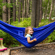 A hammock and rainbow duck boots are a tiny campers best friends in Glacier National Park, Montana.