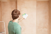 Man looking at paint colour swatches in unrenovated room back view