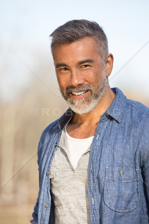 Portrait of a handsome gray haired young Asian American man outdoors