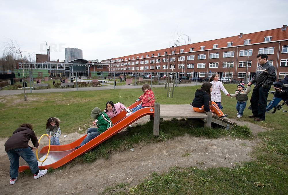 Nederland Rotterdam 8 maart 2008 20080308 .Kinderen spelen in millinxpark in achterstandswijk millinxbuurt .In de Rotterdamse Tarwewijk ligt het Millinxpark. Een groenvoorziening die te omschrijven is als teken van hoop. De Tarwewijk, een van de bekendste achterstandswijken van Rotterdam, is bezig aan een opmerkelijke metamorfose. Vijf jaar geleden startte het project om met een integrale aanpak de Millinxbuurt in de oude Rotterdamse wijk Charlois te verbeteren. Als onderdeel hiervan werd een centraal gelegen parkje, met inspraak van de buurtbewoners en met hun hulp, door de gemeente gerenoveerd. De buurt beschouwt dit als een teken van hoop. Het Millinxpark nadert nu zijn voltooiing. Plant Publicity Holland (PPH) en de Vereniging Hoveniers en Groenvoorzieners (VHG) hebben tesamen met de wijkraad zich ingezet om met planten en arbeid het parkje een echt groen aanzien te geven. Vrijdag 4 juni wordt de beplanting officieel aan de burgemeester van Rotterdam, mr I.W. Opstelten aangeboden. Dit gebeurt door de heer J. Habets directeur van Plant Publicity Holland..?.De overdracht valt samen met de officiële ingebruikneming van het Millinxhuis..Groen is de motor?De aandacht voor het groen is de motor geweest voor een opwaardering van de buurt. Rond het Millinxpark zijn huizenblokken gerenoveerd. Het project had een duidelijke positieve spin-off. De buurtbewoners voelden zich betrokken en werden zelf ook actief om het aanzien van hun buurt te verbeteren. De waarde van de panden is gestegen, de grotere sociale controle heeft ondermeer geleid tot een beter leefklimaat. Het is de bedoeling om het groen in de Tarwewijk verder op te waarderen met een lange groenstrook , die als een ruggengraat door de buurt loopt. Het beschikbaar krijgen van de benodigde financiële middelen en het vasthouden en stimuleren van de interesse bij de gemeentelijke overheid is nu essentieel in deze fase.Het is nu van belang dat het belang van het groen ook bestuurlijk wordt onderbouwd. Het projectbure