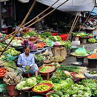 Vietnamese Vegetable Market in Hue, Vietnam<br /> Vietnam is the world's third largest producer of vegetables with over 120 different species.  Yet, most of this is grown on small farms and over 80% of them sell their own crop.  The marketing is typically done by Vietnamese women in open markets like the one shown in Hue, Vietnam.    The produce is displayed helter-skelter in baskets, boxes, bowls and mats on top of rickety shelves or on the dirty ground.