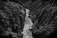 The rain-swollen and muddy Rio Pastazo, draining the Andes, thunders through a narrow canyon of volcanic cliffs as it leaves the highlands and drops into the long series of canyons that deliver the glacier melt to the Amazon Basin.  Ecuador.