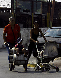 March 28, 2019 - Los Guayos, Carabobo, Venezuela - March 28, 2019. children, bottle, mothers, wheelbarrow, shortage, crisis, the guayos, carabobo, venezuela, A girl takes advantage of wandering in a wheelbarrow, while her mother goes to look for gas, in the municipality of Los Guayos Carabobo. Photo: Juan Carlos Hernandez (Credit Image: © Juan Carlos Hernandez/ZUMA Wire)