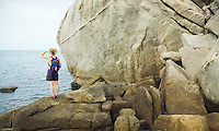 Woman standing amid granite boulders at waterfront&#xA;<br />
