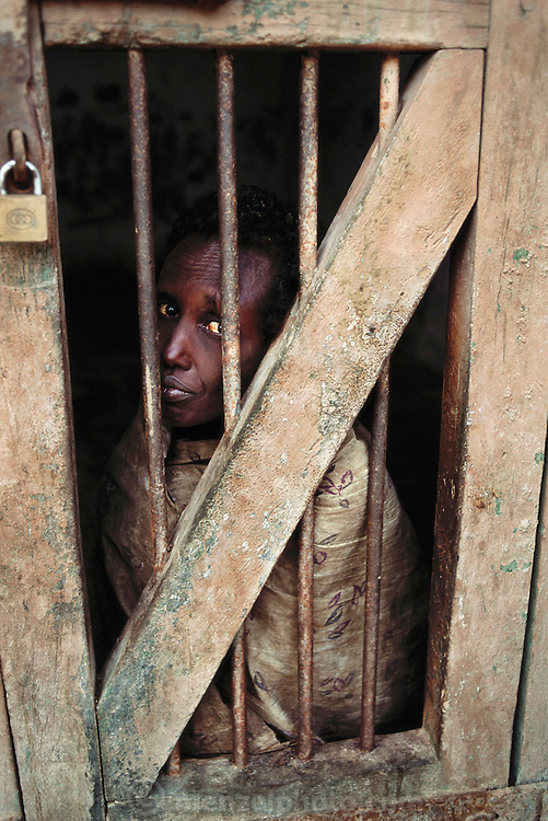 """A mental hospital built by the British in the 1930's. The hospital is named """"Jail Magnoun"""" which is Arabic for """"mad"""". Once a patient is committed to the hospital there is no chance of release. Some patients, like the one pictured, are caged or chained. Berbera, Somaliland."""
