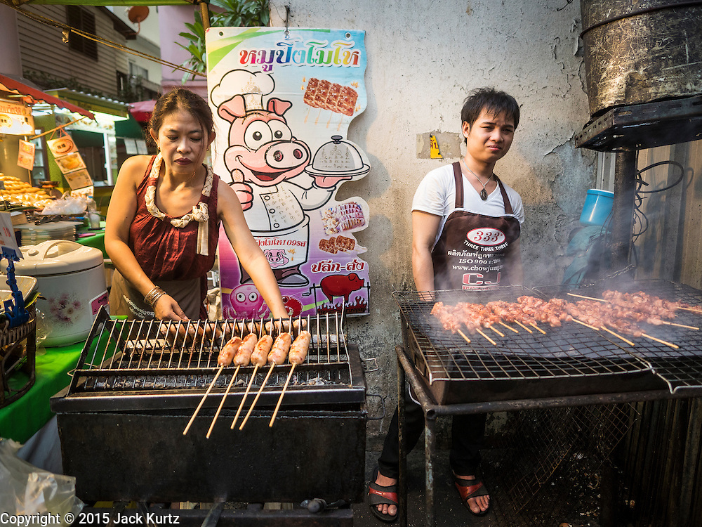 26 MAY 2015 - BANGKOK, THAILAND:  Grilled pork and sausage vendors on Sukhumvit Soi 38, one of the most famous street food areas in Bangkok. The food carts and small restaurants along the street have been popular with tourists and Thais alike for more than 40 years. The family that owns the land along the soi recently decided to sell to a condominium developer and not renew the restaurant owners' leases. More than 40 restaurants and food carts will have to close. The first wave of closings could start as soon June 21 and all of the restaurants are supposed to close over the next several months.    PHOTO BY JACK KURTZ