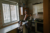 "SUTERA, ITALY - 8 JANUARY 2018: Margareth (30), a Nigerian asylum seeker who arrived in Sutera in 2015, cooks lunch with her two children in her apartment, in Sutera, Italy, on January 8th 2018.<br /> <br /> Sutera is an ancient town plastered onto the side of an enormous monolithic rock, topped with a convent, in the middle of the western half of Sicily, about 90 minutes by car south of the Sicilian capital Palermo<br /> Its population fell from 5,000 in 1970 to 1,500 today. In the past 3 years its population has surged  after the local mayor agreed to take in some of the thousands of migrants that have made the dangerous journey from Africa to the Sicily.<br /> <br /> ""Sutera was disappearing,"" says mayor Giuseppe Grizzanti. ""Italians, bound for Germany or England, packed up and left their homes empty. The deaths of inhabitants greatly outnumbered births. Now, thanks to the refugees, we have a chance to revive the city.""<br />  Through an Italian state-funded project called SPRAR (Protection System for Refugees and Asylum Seekers), which in turn is co-funded by the European Union's Fund for the Integration of non-EU Immigrants, Sutera was given financial and resettlement assistance that was co-ordinated by a local non-profit organization called Girasoli (Sunflowers). Girasoli organizes everything from housing and medical care to Italian lessons and psychological counselling for the new settlers.<br /> The school appears to have been the biggest beneficiary of the refugees' arrival, which was kept open thanks to the migrants.<br /> Nunzio Vittarello, the coordinator of the E.U. project working for the NGO ""I Girasoli"" says that there are 50 families in Sutera at the moment."