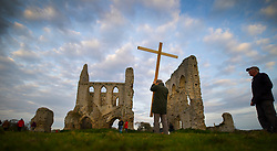 © Licensed to London News Pictures. 16/04/2017. Ripley, UK. A parishioner carries away a temporary cross after attending an Easter Sunday dawn service in the ruins of Newark Priory. The priory, which was established towards the end of the 12th century, lies near the banks of the River Wey and is only accessible once a year at Easter.  Photo credit: Peter Macdiarmid/LNP