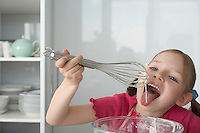 Girl (5-6) licking cream from wire whisk