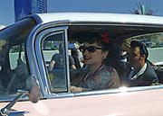 A tattooed Rockabilly girl is driving a pink Hotrod, Viva Las Vegas Festival, Las Vegas, USA 2006.