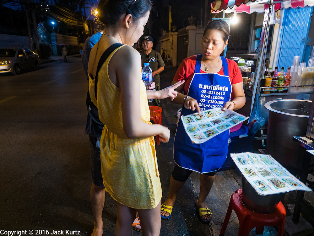 17 JANUARY 2016 - BANGKOK, THAILAND: People look at the menu of a noodle shop on Sukhumvit Soi 38, one of the most famous street food areas in Bangkok. The food carts and small restaurants along the street have been popular with tourists and Thais alike for more than 40 years. The family that owns the land along the soi recently decided to sell to a condominium developer and not renew the restaurant owners' leases. More than 40 restaurants and food carts will have to close. Most of the restaurants on the street closed during the summer of 2015. The remaining restaurants are supposed to close by the end of this week.           PHOTO BY JACK KURTZ