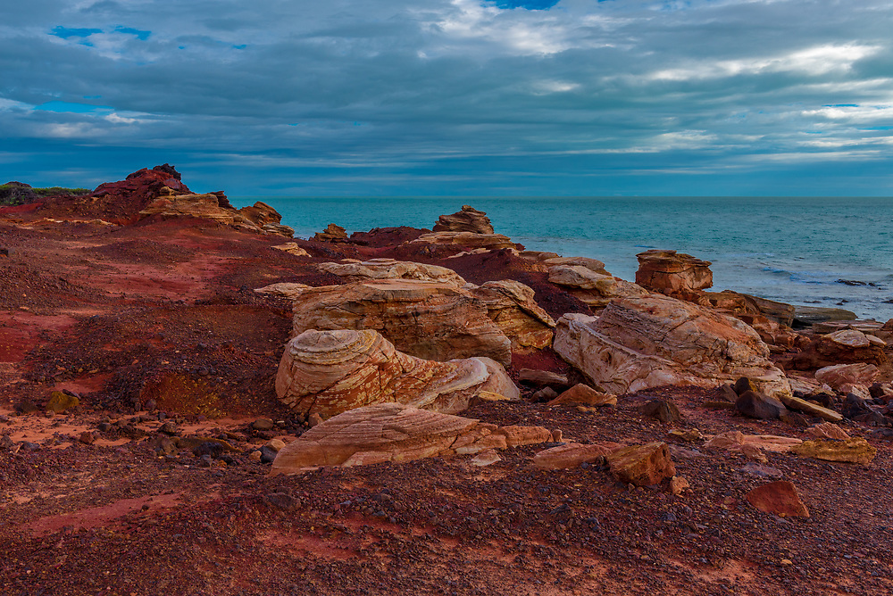 A bright red rock formation contrasts woith a blue sky and acqua colored waters.