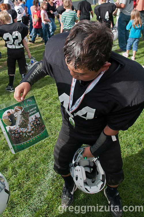 Keegan Mizuta shows his team picture following the Vale Broncos vs Vale Cowboys in the Eastern Oregon Youth Football Championship game at Frank Hawley Stadium in Vale, Oregon on October 13, 2012.