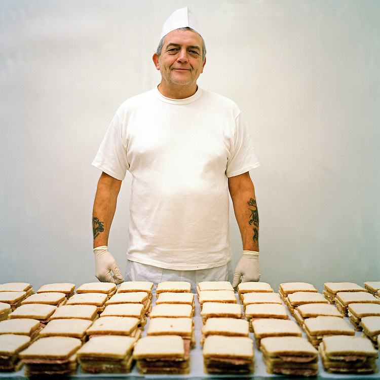 Stan, a kitchen orderly, making corned beef sandwiches for packed lunches. £ 11.40 per week. HMP Coldingley, Surrey was built in 1969 and is a Category C training prison. Coldingley is focused on the resettlement of prisoners and all prisoners must work a full working week within the prison. Its capacity is 390 prisoners.