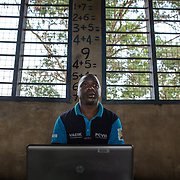 Data clerk Oscar Kai (blue shirt), at the Ngamani Primary School for an outreach health clinic. Oscar will enter data about the PCV 10 vaccine, as well as pentavalent, BCG, polio, yellow fever, measles, diphtheria, tetanus and hepatitis B immunizations. All of that fresh information is then uploaded to portable hard-drives that are returned weekly to the study headquarters, where the database is updated.<br /> <br /> &quot;Because the database is digitized, it means it's far easier to keep our records fresh, even if children move and access health services in different locations,&quot; says Dr.Benjamin Tsofa, the Kenyan health ministry's chief liaison on the study. <br /> <br /> In January 2011, the Kenyan government with support from the GAVI Alliance, introduced a new vaccine, PCV-10, which targets 10 bacteria than can cause Invasive Pneumococcal Disease.The vaccine's impact is monitored through an electronic database, part of the GAVI funded PCV impact study, which maps the growing coverage of the new vaccine. Already, here in Kilifi, the incidence of the illness in children aged five has gone down by approximately two-thirds.