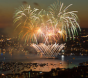 """Spectacular fireworks explode over Gasworks Park, witnessed by a large audience of boats in Union Bay, at dusk July 4, 2007 in Seattle, Washington, USA. Published in """"Light Travel: Photography on the Go"""" by Tom Dempsey 2009, 2010."""