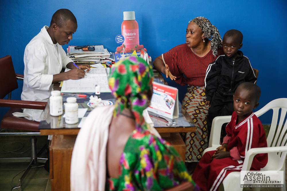 Katy Cherif, 40, and her twin sons Lacine (left) and Lusseini, both 4 and suffering from malaria and diarrhea, meet with a nurse at the Libreville health center in Man, Cote d'Ivoire on Wednesday July 24, 2013. Center bottom is Katy's mother Matila Cherif, 60.