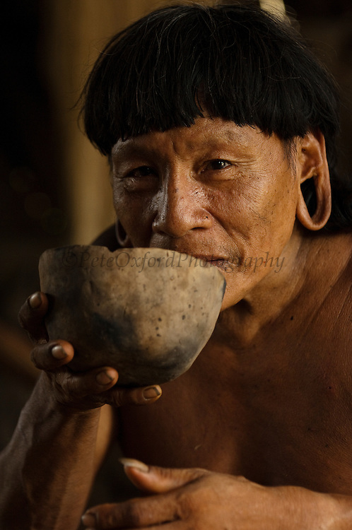 Huaorani Indian - Menga Darita drinking chicha from a ceramic bowl. Gabaro Community. Yasuni National Park.<br /> Amazon rainforest, ECUADOR.  South America<br /> Chicha is a local 'beer' made from yucca. The Huaorani also make their own ceramic bowls.<br /> This Indian tribe were basically uncontacted until 1956 when missionaries from the Summer Institute of Linguistics made contact with them. However there are still some groups from the tribe that remain uncontacted.  They are known as the Tagaeri &amp; Taromanani. Traditionally these Indians were very hostile and killed many people who tried to enter into their territory. Their territory is in the Yasuni National Park which is now also being exploited for oil.