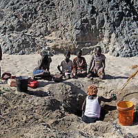 Africa, Namibia, Kunene. Himba People digging a well.