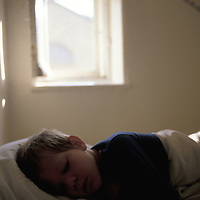 A young boy takes a nap during daytime.