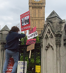 Parliament Square, Westminster, London, June 27th 2016. Thousands of Labour's Momentum members and their supporters gather in Parliament Square in a display of support for embattled Labour Leader Jeremy Corbyn as he suffers numerous calls for his resignation by party members, saying he has does not have the authority to lead the divided party, following his less than emphatic support for Remain in the EU referendum. PICTURED: A man attaches a placard to the railings surrounding the Houses of Parliament.