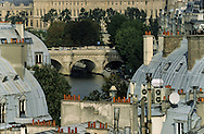 France. Paris. 5th district. Elevated view on the roofs and  the Seine River . In the distance the Louvre museum