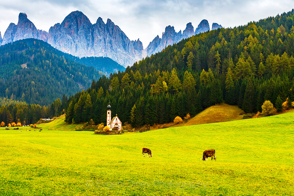 Small church located in a meadow with high mountain peaks behind