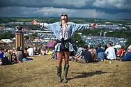A festival-goer enjoys a moment of sunshine before the rain, on the hill overlooking Glastonbury Festival