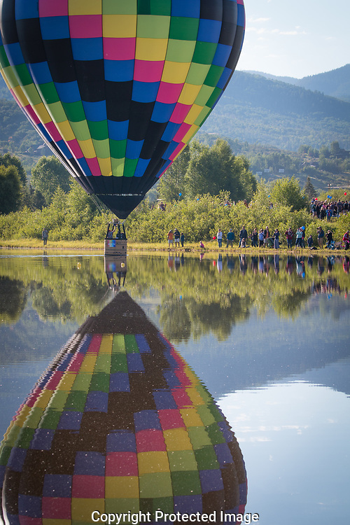 Hot air balloons are reflected in the waters of Bald Eagle Lake, Steamboat Springs, CO, during the annual Hot Air Balloon Rodeo.