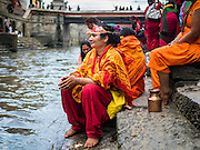03 AUGUST 2015 - KATHMANDU, NEPAL:      Hindu women make a pilgrimage and pray on the banks of the Bagmati River at Pashupatinath, a complex of important Hindu temples in Kathmandu. The Bagmati River runs through the complex. It is Nepal's most holy river, and this stretch of the river is like Varanasi in India. The river bank is lined with cremation ghats. Many Hindus, from both Nepal and India, make pilgrimages to Pashupatinath.   PHOTO BY JACK KURTZ