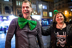 © Licensed to London News Pictures . 18/03/2017 . Cardiff , UK. A man wearing a large , novelty green bowtie with a woman wearing a tiny novelty green hat . Revellers on a windy and wet Saint Patrick's Day night out in Cardiff city Centre . Photo credit: Joel Goodman/LNP