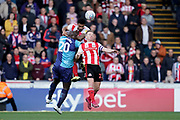Joel Lynch of Sunderland heads the ball above Adebayo Akinfenwa of Wycombe Wanderers during the EFL Sky Bet League 1 match between Wycombe Wanderers and Sunderland at Adams Park, High Wycombe, England on 19 October 2019.