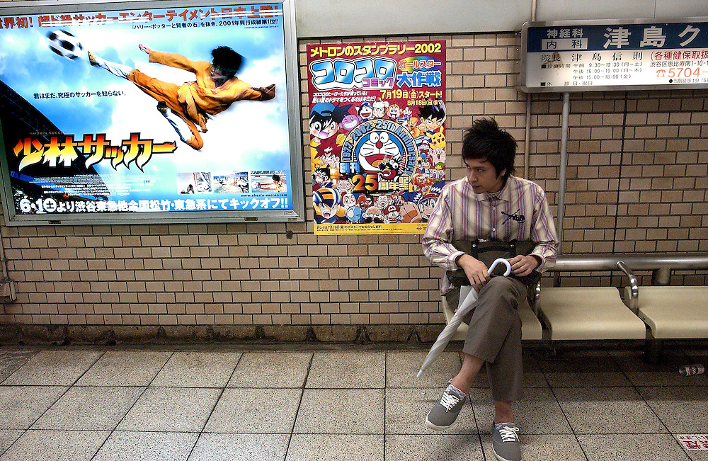 A man sits in a subway waiting for a train next to a film poster advertising a new Asian film called 'Shaolin Soccer'. Tokyo Japan 26/06/02...©David Dare Parker/AsiaWorks Photography