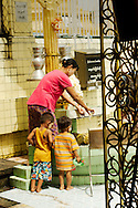 Mother pouring water over statue with children at Yangon pagoda