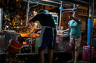 A street food hawker fries char koay teow over charcoal. George Town, Malaysia July, 2013