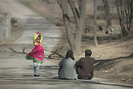 A girl wearing a traditional Choson-ot dress dances while her parents look on, at Moranbong Park, Pyongyang, North Korea