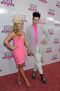 Tara Lipinski and Johnny Weir pose on the pink carpet on Longines Kentucky Oaks Day, Friday, May 6, 2016, in Louisville, Ky.  Longines, the Swiss watch manufacturer known for its luxury timepieces, is the Official Watch and Timekeeper of the 142nd annual Kentucky Derby. (Photo by Diane Bondareff for Longines/AP Images)