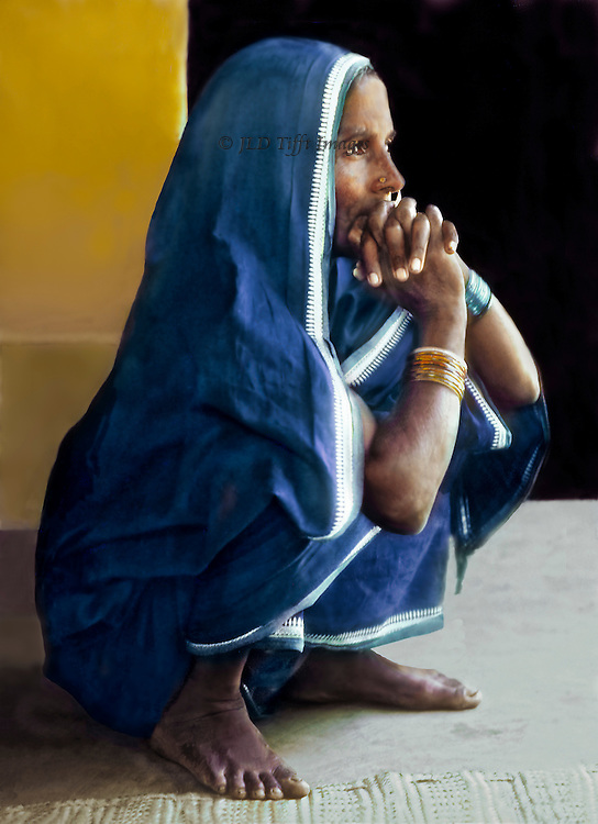 Bangladeshi woman wearing a blue sari and bracelets hunkers down, hands clasped before her face, in Old Dhaka.  She is thinking, contemplating, waiting, resting...