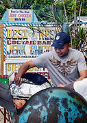 Jamaican man prepares jerk chicken in an oil barrel grill, Negril, Jamaica