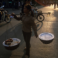 Asia, Vietnam, Hanoi, Woman carries traditional baskets through streets near Hoan Kiem Lake in city's Old Quarter