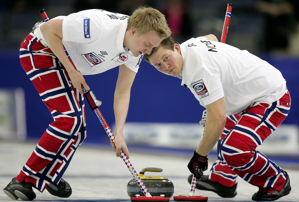 Norway's lead Haavard Vlad Petersson and second Christoffer Svae sweep skip Thomas Ulsrud's shot during their 3-4 page playoff match against Sweden at the Ford World Men's Curling Championships in Regina, Saskatchewan, April 9, 2011.<br /> AFP PHOTO/Geoff Robins