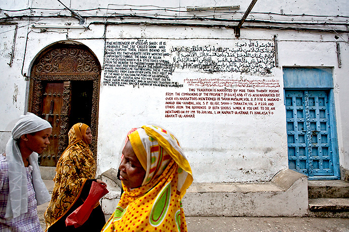 Three women walking by a Stonetown mosque, its walls covered with quotations and moral precepts.