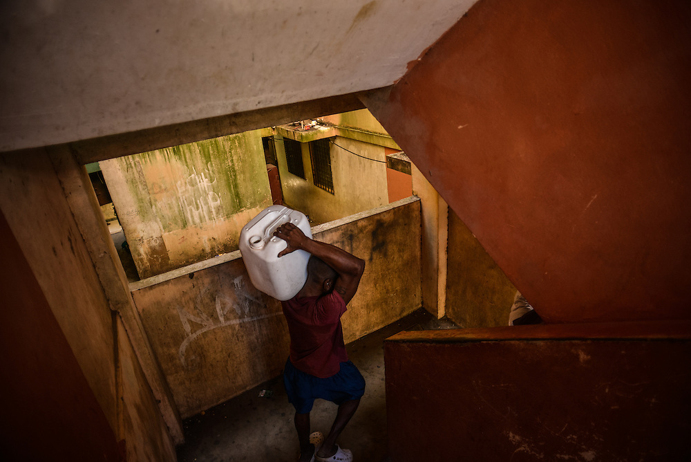A resident of a low-income government housing project in Colón, Panama, carries a large jug of water to fill it up at a nearby car wash, in order to have water in his apartment in Colón, Panama because the building has not had running water in over a week. Residents complain of rarely having basic working municipal services, such as water, electricity and waste removal.  Despite being the second largest city in Panama, Colón is one of the poorest in the region, and its residents suffer from a critical shortage of potable water, sewer connections and housing--many people live in condemned or should be condemned buildings. Panama is now one of the fastest growing countries in Latin America and there is a growing resentment and impatience that Colón has not reaped as much of the benefit as Panama City. Much of the improvements in Colón have only focused on the Colón Free Trade Zone, a duty free collection of shops, that cater to cruise ship tourists.