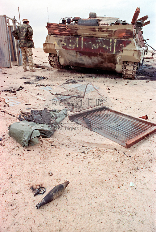 A Qatar soldier inspects an Iraqi armored personnel carrier destroyed by U.S Forces during the Battle of Khafji February 2, 1991 in Khafji City, Saudi Arabia. The Battle of Khafji was the first major ground engagement of the Gulf War.