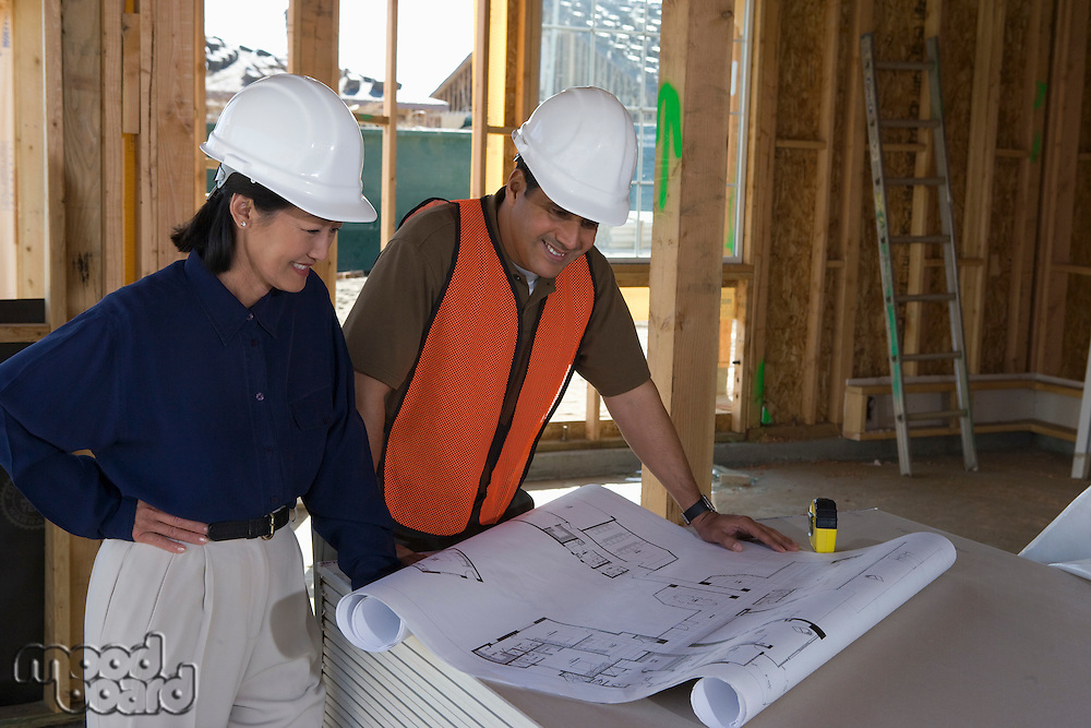 Architect and construction worker looking at blueprints inside half constructed house