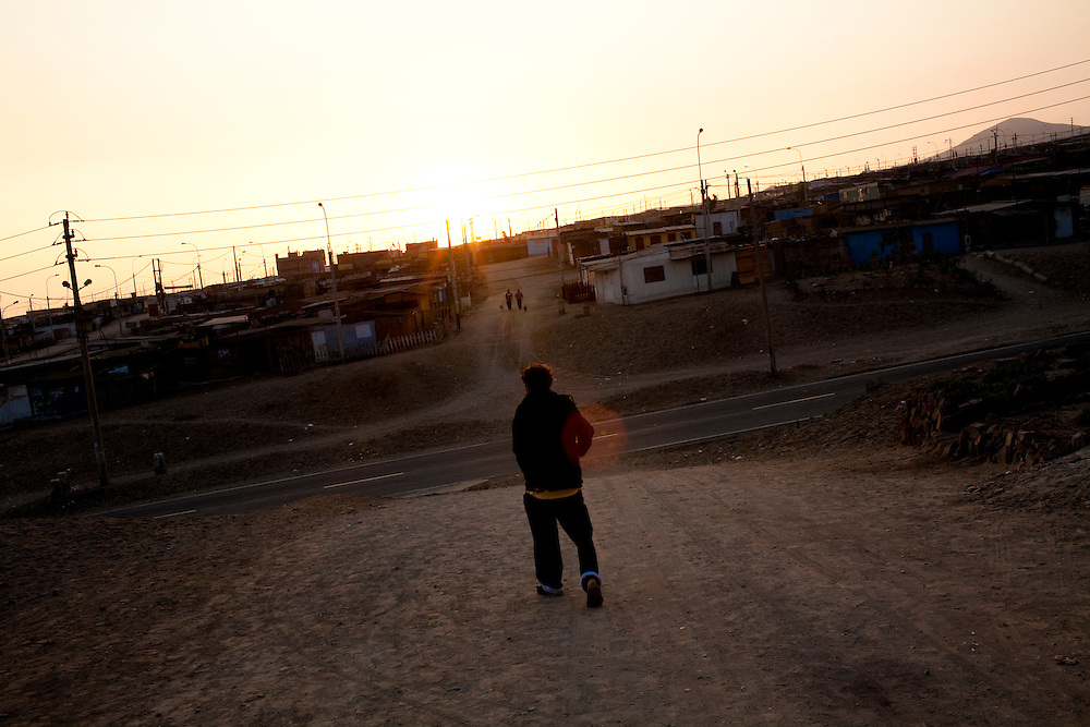 A man walks toward the road at sunset on Thursday, Apr. 16, 2009 in Ventanilla, Peru.