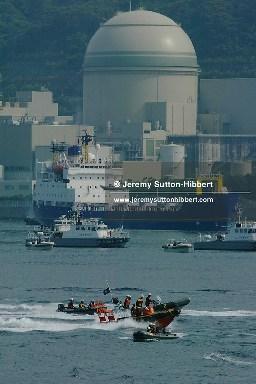 """SURROUNDED BY JAPANESE POLICE AND COAST GUARD GREENPEACE INFLATABLES """"PROTEST"""" ( bear witness...) ,  IN UCHIURA BAY, BESIDE THE TAKAHAMA NUCEAR PLANT, AS BNFL SHIP 'PACIFIC PINTAIL' DEPARTS LATE AFTERNOON AFTER COLLECTING REJECTED PLUTONIUM MOX FUEL, FOR SHIPMENT BACK TO THE UNITED KINGDOM. TAKAHAMA, JAPAN. 04/07/02. .PIC © JEREMY SUTTON-HIBBERT/GREENPEACE 2002..*****ALL RIGHTS RESERVED. RIGHTS FOR ONWARD TRANSMISSION OF ANY IMAGE OR FILE IS NOT GRANTED OR IMPLIED. CHANGING COPYRIGHT INFORMATION IS ILLEGAL AS SPECIFIED IN THE COPYRIGHT, DESIGN AND PATENTS ACT 1988. THE ARTIST HAS ASSERTED HIS MORAL RIGHTS. *******"""