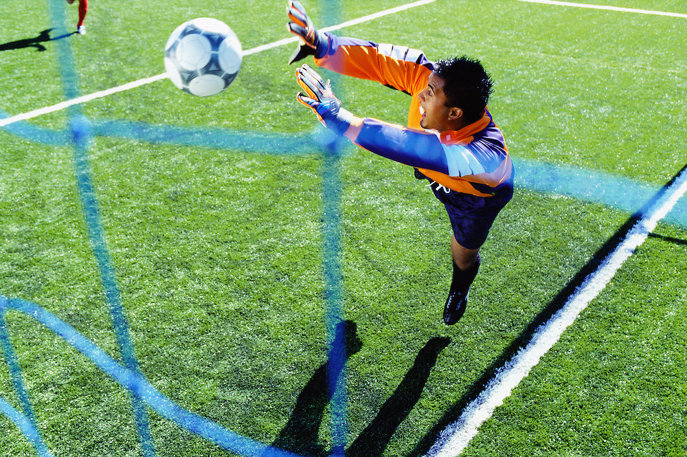 A Hispanic goalie diving to block a shot on goal.