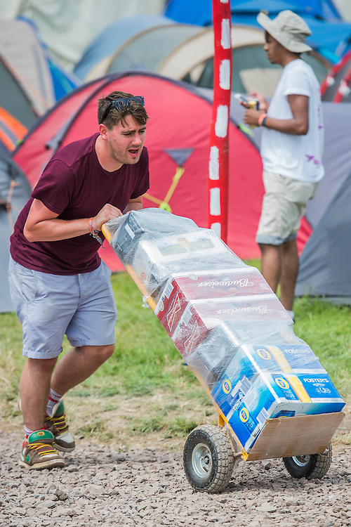 Arrivals face blistering heat as they struggle in with their kit and vital stocks of beer. The 2015 Glastonbury Festival, Worthy Farm, Glastonbury.