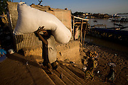 People unloading a boat in Mopti's harbour. At the confluence of the Niger and the Bani rivers, between Timbuktu and Segou, Mopti is the second largest city in Mali, and the hub for commerce and tourism in this west-african landlocked country.